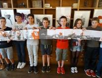 """Les enfants visitent l'exposition et m'aident à déplier l'album """"Promenons-nous, dans les bois"""", qui fait plus de cinq mètres, dans sa version leporello."""